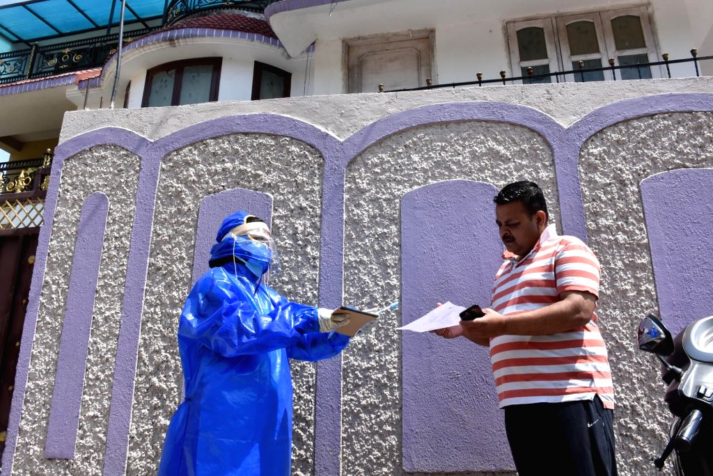 A health worker wearing protective gear collects sample from a person at Hindpidi area of Ranchi for coronavirus tests, on Apr 1, 2020. Jharkhand on Tuesday reported its first COVID-19 ...