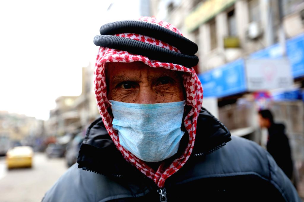 A Jordanian wearing face mask walks in a street in Amman, Jordan, March 19, 2020. The Jordanian armed forces said on Wednesday that all entrances to the capital ...