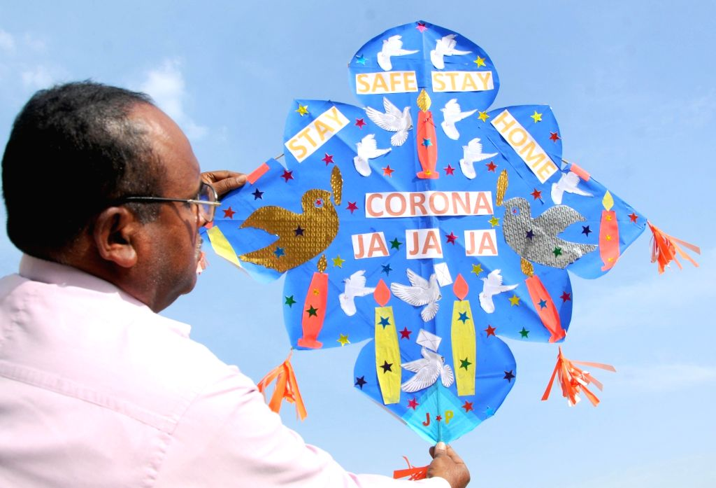 A kite-maker shows a kite prepared by him carrying messages urging people to stay safe by staying at home to keep themselves protected from COVID-19 amid coronavirus pandemic, in Amritsar ...