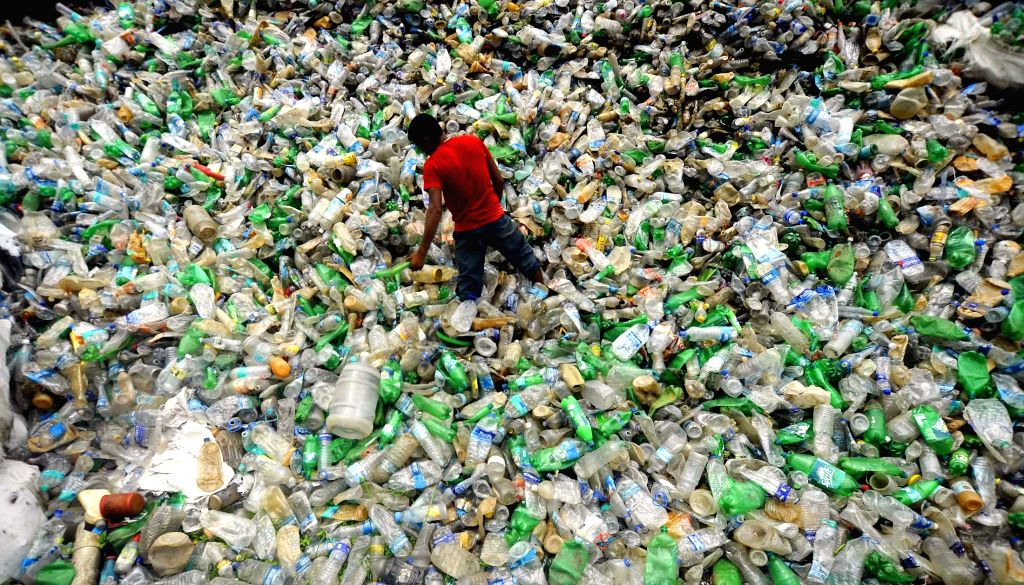 :A labour stands on a heap of plastic bottles at a recycling plant on the eve of World Environment Day in Agartala on June 4, 2014. (Photo: IANS).