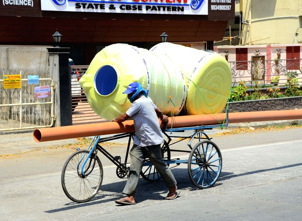 A labourer carries water tanks on a hot sunny day in Nagpur, on May 1, 2019. May 1 is observed as International Labour Day.