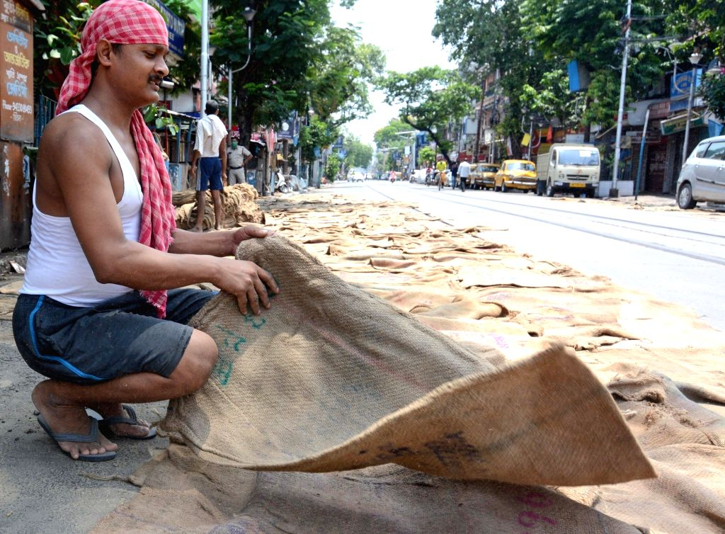 A labourer puts jute sacks to dry at a pavement besides a deserted Kolkata street during the extended nationwide lockdown imposed to mitigate the spread of coronavirus on May 7, 2020.