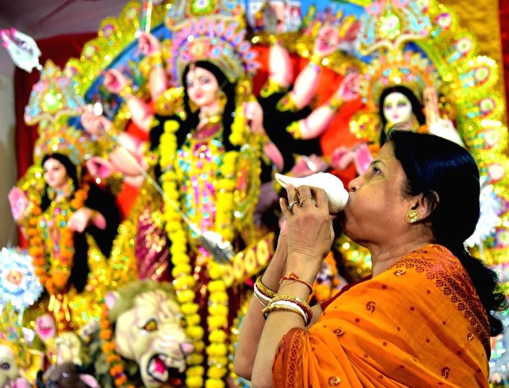 A lady blows a conch shell at a Durga Puja Pandal in Bikaner of Rajasthan on Oct 8, 2016.