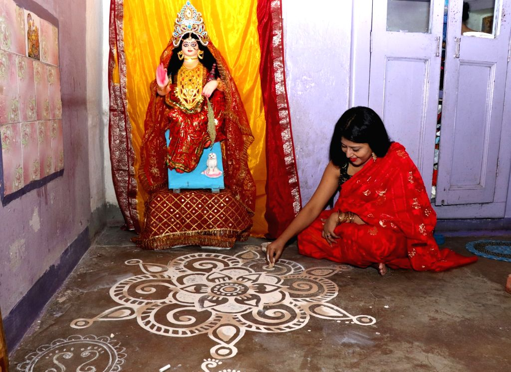 A lady busy making 'alpana' - colourful motifs on the eve of Lakshmi Puja in Kolkata on Oct 12, 2019.