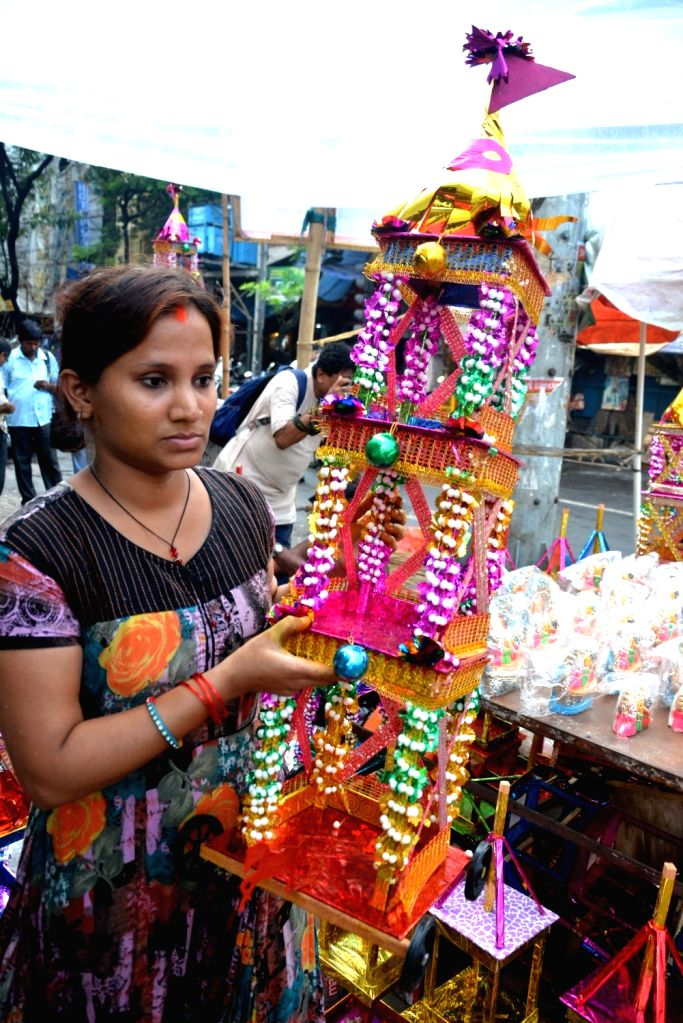 A lady carries a rath -chariot- on the eve of Jagannath Rath Yatra in Kolkata, on July 13, 2018.