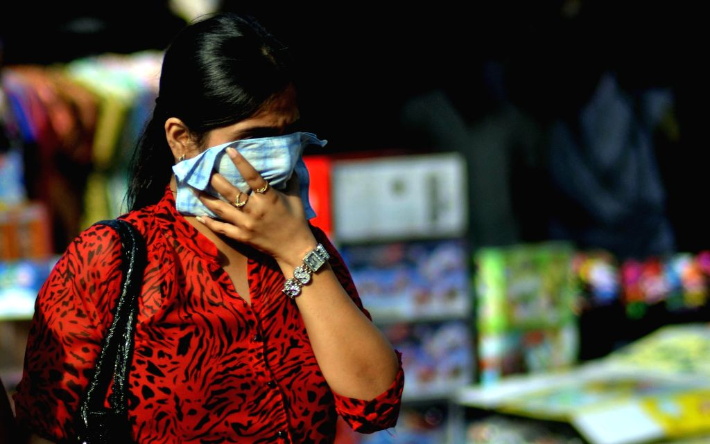 A lady covers her face to avoid direct exposure to sunlight on a hot afternoon in Kolkata on May 15, 2014.