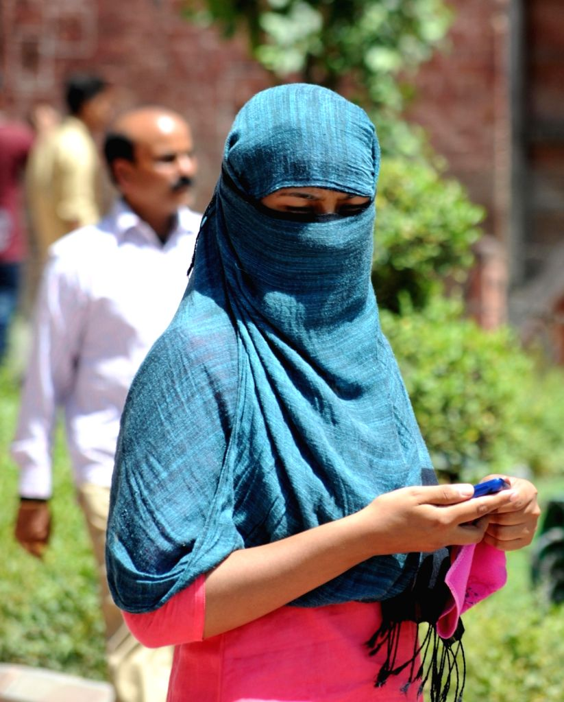 A lady covers her face to avoid scorching sun on a hot day in Amritsar on May 17, 2016.