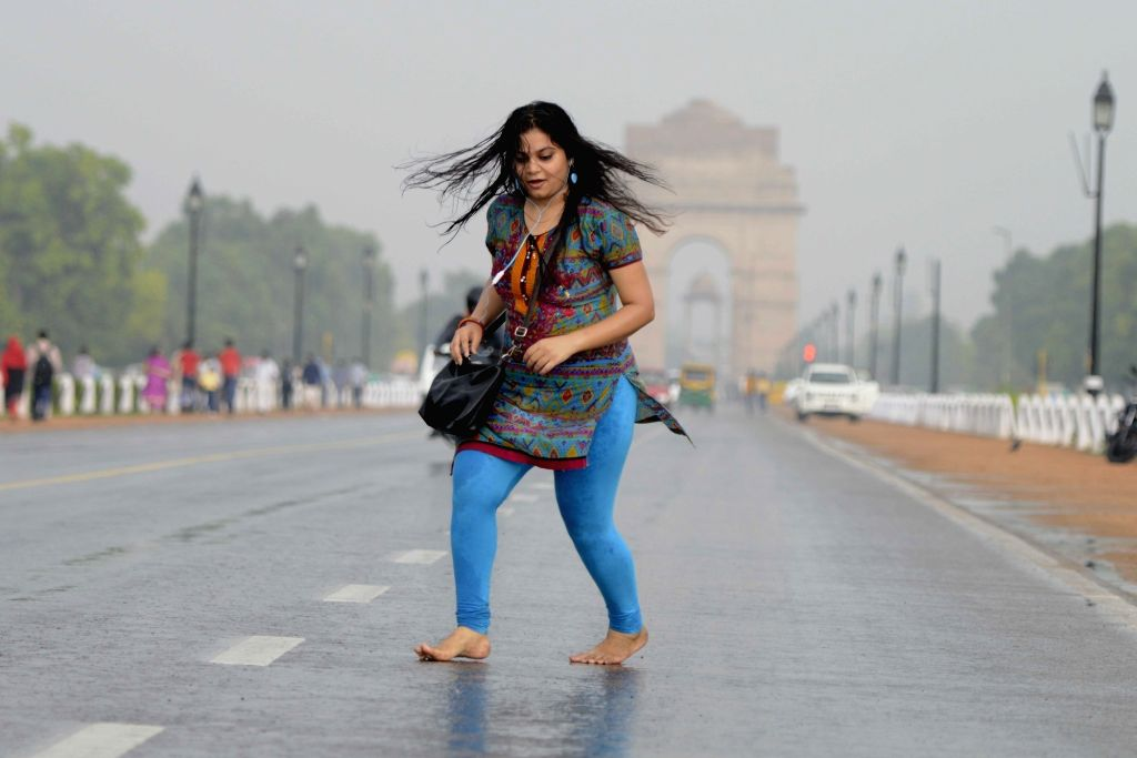 A lady enjoys rains at Rajpath in New Delhi, on May 30, 2016.