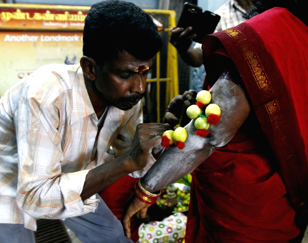 A lady gets her hand threaded with lemons on the third day of Aadi Perukku in Chennai, on Aug 5, 2016.