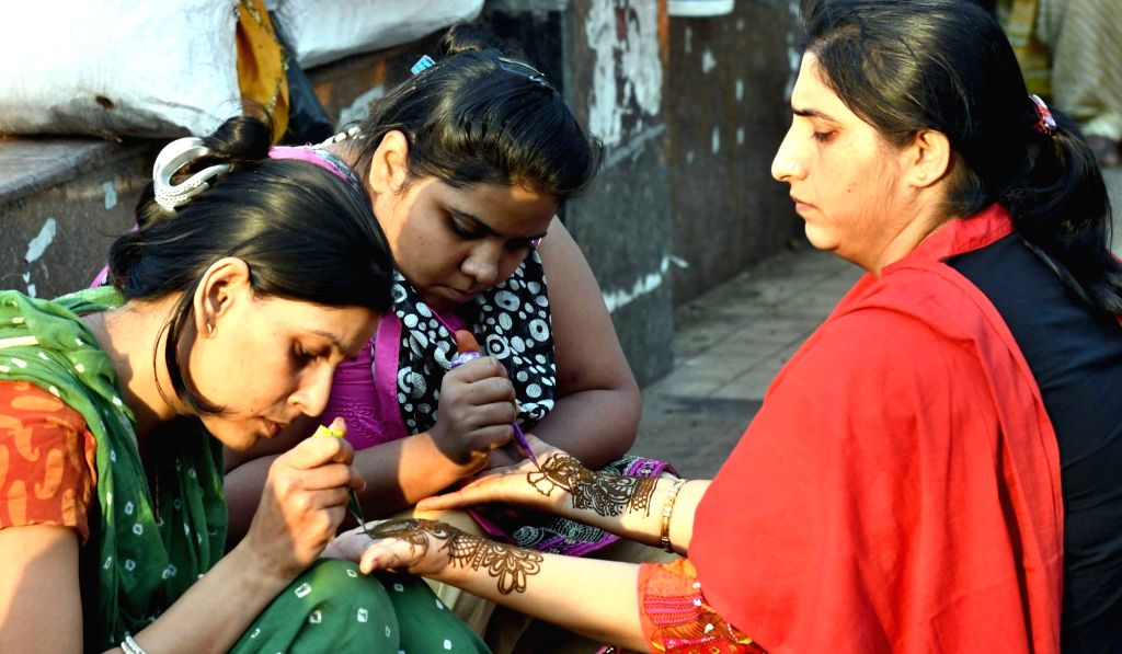 A lady gets mehndi applied on mehndi applied on her palm on the eve of Karva Chauth in New Delhi, on Oct 18, 2016.