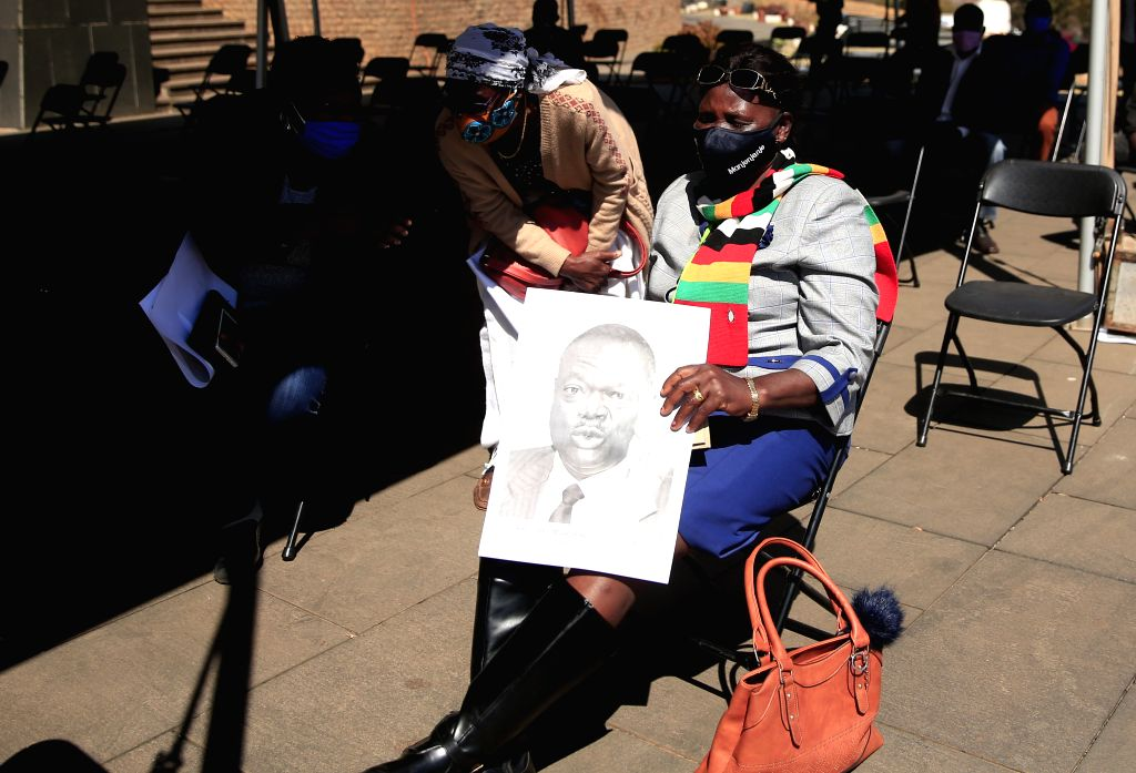 A lady holds a portrait of late Zimbabwean Agriculture Minister Perrance Shiri during his burial at the National Heroes Acre in Harare, Zimbabwe, on July 31, 2020. ... - Perrance Shiri