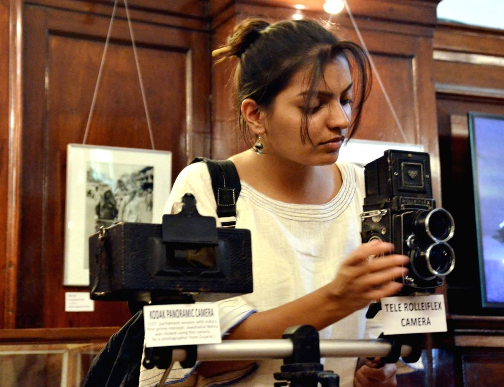 A lady looks at a camera at 'A Vintage Camera Collection'  a  camera exhibition organised at IGNCA on World Photography Day in New Delhi on Aug 19, 2014.