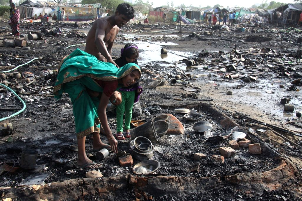 A lady looks for her belongings after a fire reduced her home to ashes near Daulatabad in Gurugram on June 3, 2017. More than hundred houses were destroyed in the fire.