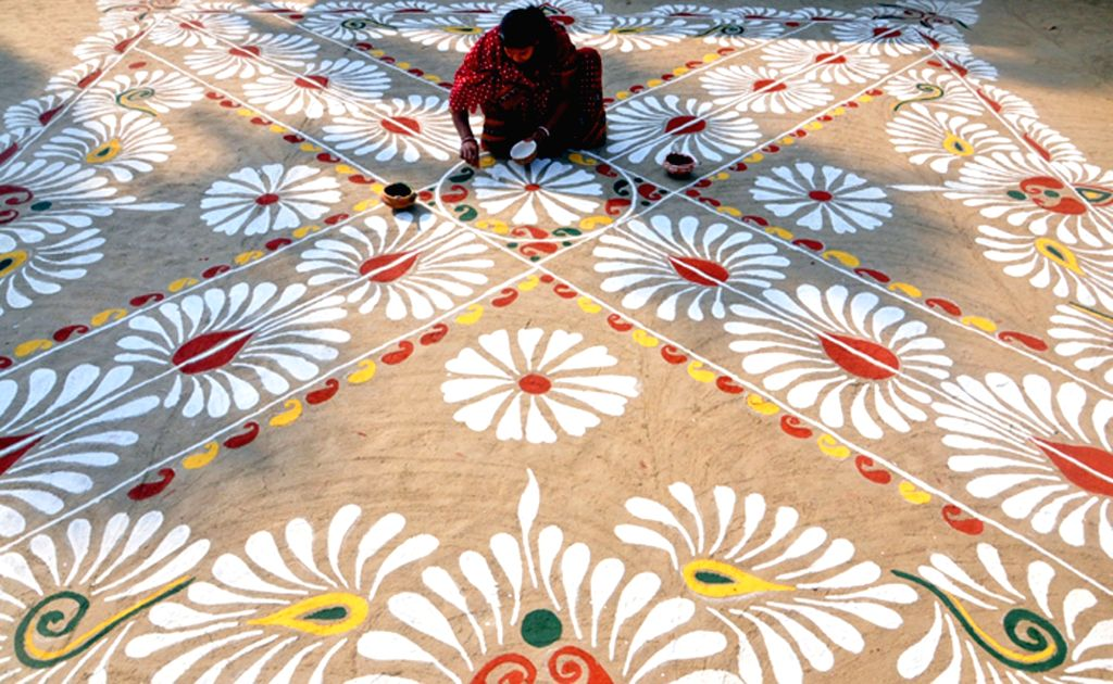 "A lady makes ""alpana"" - colourful motifs, on the eve of ""Makar Sankranti"" on the outskirts of Agartala on Jan 13, 2016."