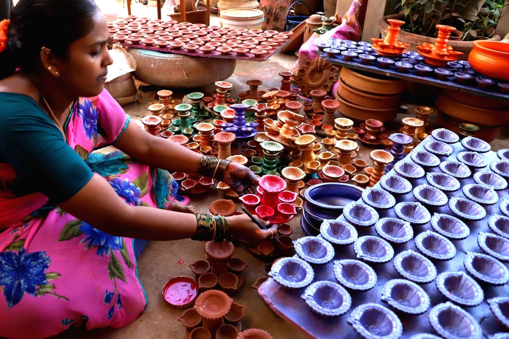 A  lady paints earthen lamps ahead of 'Diwali' in Bengaluru on Oct 31, 2018.
