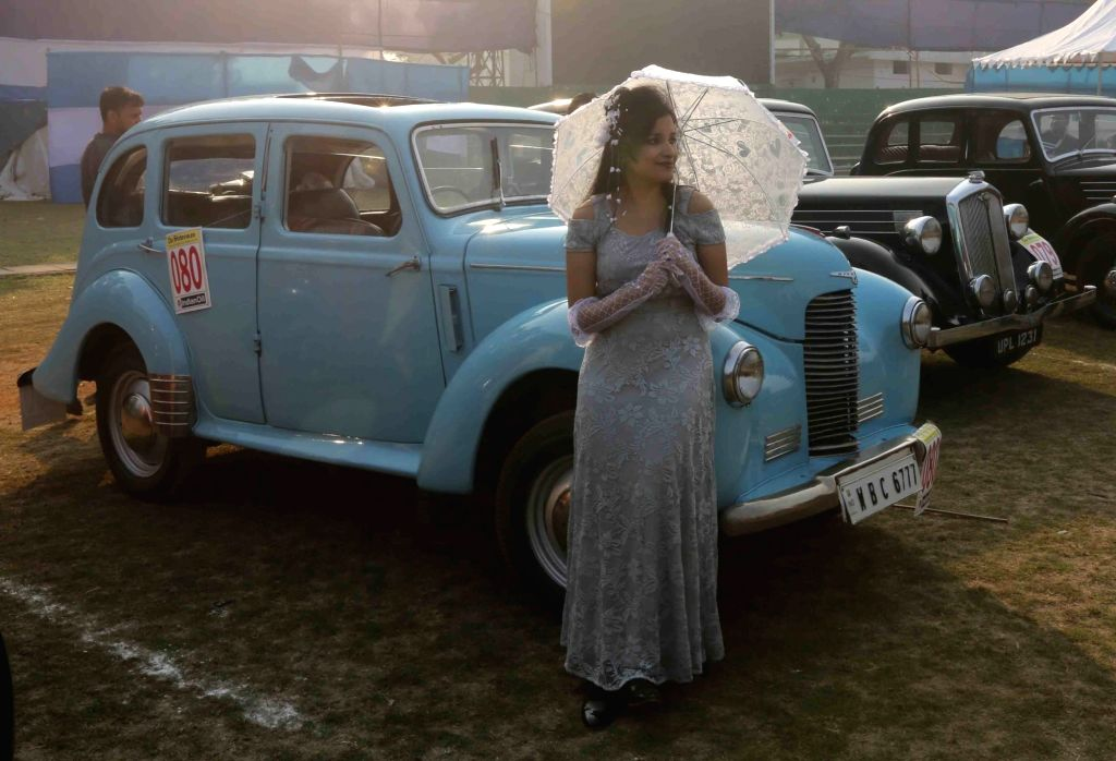 A lady poses in front of a vintage car during vintage motor vehicle rally in Kolkata, on Feb 3, 2019.