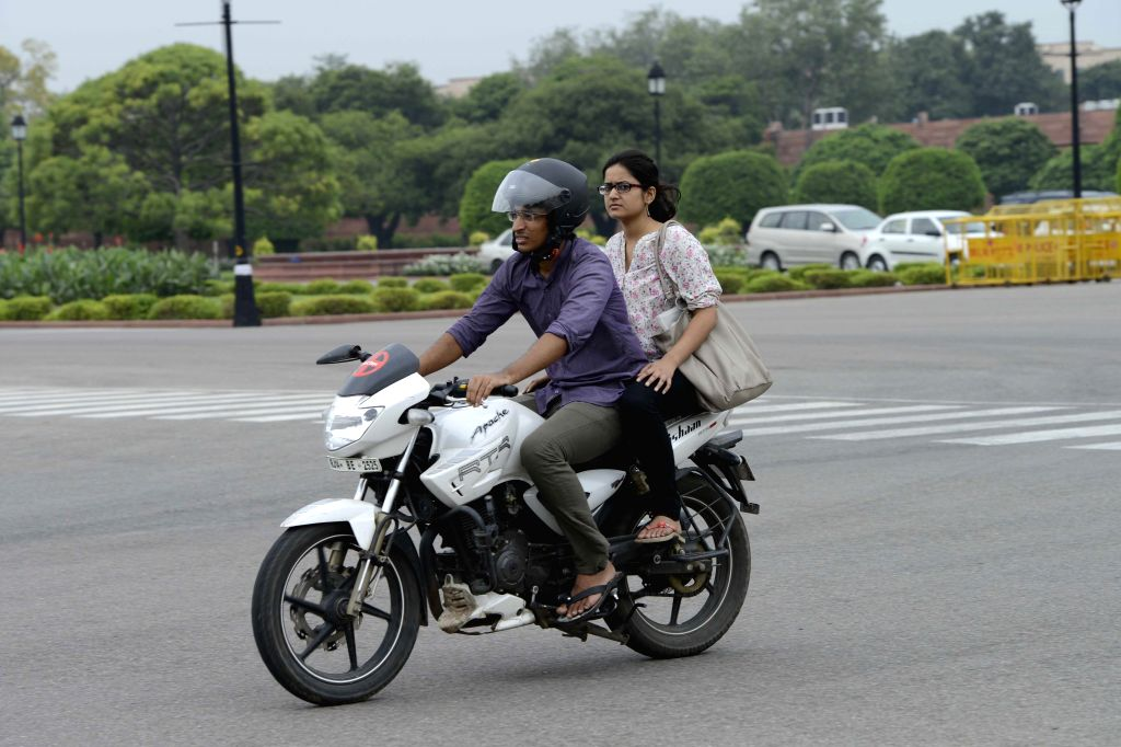 A lady rides pillion on a bike without wearing helmet in New Delhi on Aug 29, 2014. The Delhi government has issued a notification making wearing of helmets mandatory for women with immediate effect. (Photo: IANS)