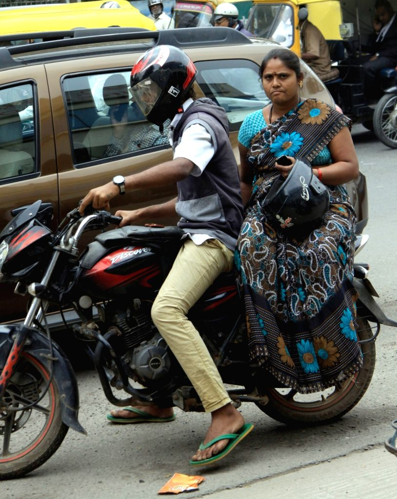 A lady riding pillion on a scooter ignores the new helmet rule, that mandates that all riders and their pillions have to compulsorily wear the protective headgear, in Bengaluru, on Jan 20, ...