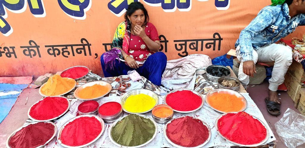A lady sells coloured powder during Kumbh at Sangam in Prayagraj.