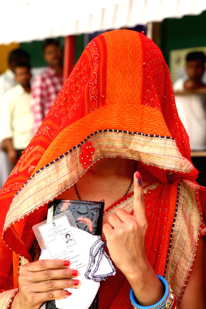 A lady shows her voter identity card at a polling booth during the sixth phase of 2019 Lok Sabha elections, in New Delhi on May 12, 2019.