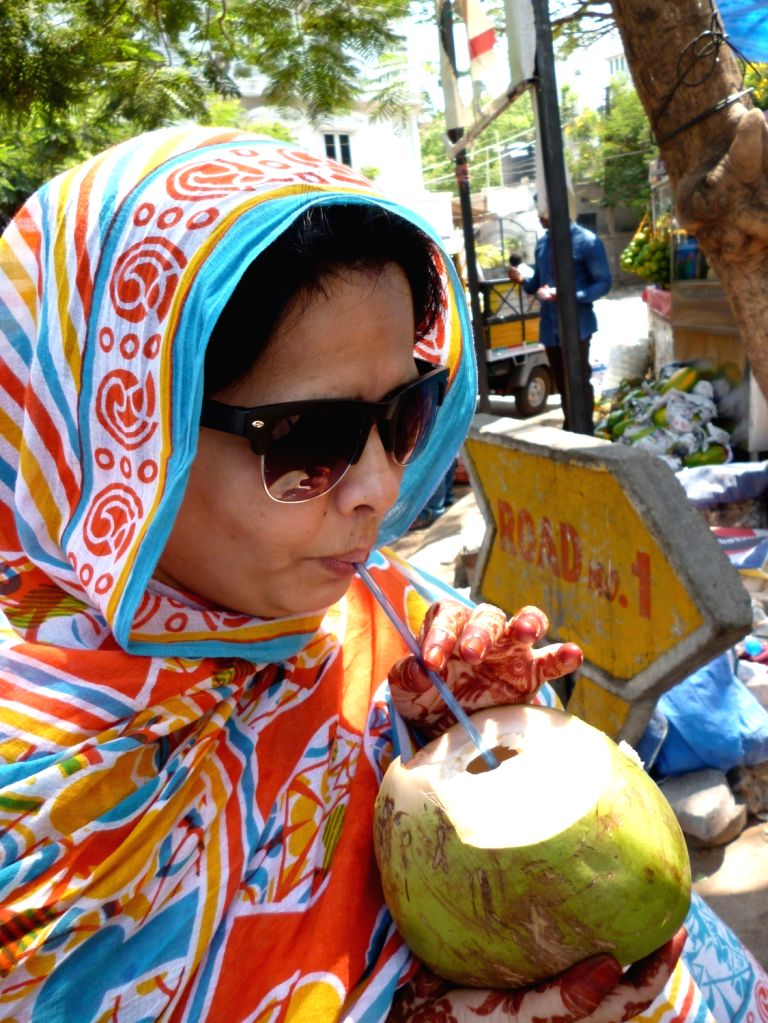 A lady sips coconut water on a hot day in Hyderabad on April 11, 2016.