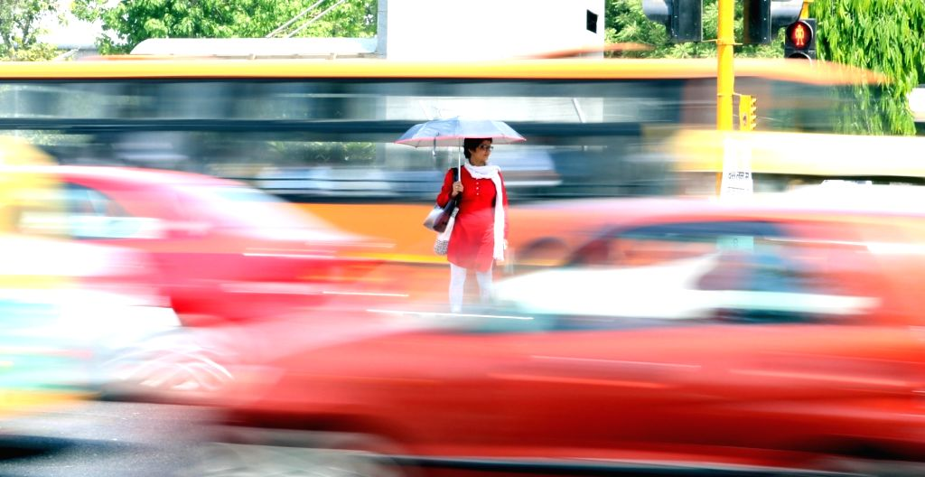 A lady tries to cross a busy Delhi road, on April 18, 2016.