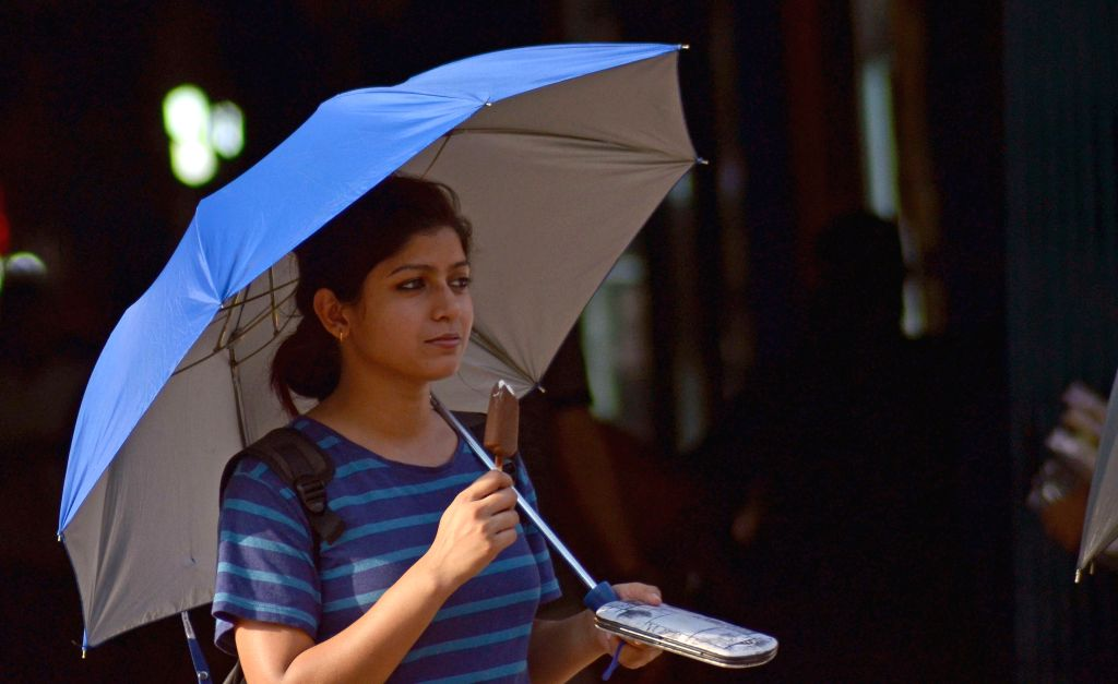 A lady uses an umbrella to shield themselves form direct sunlight on a hot afternoon in Kolkata on May 15, 2014.