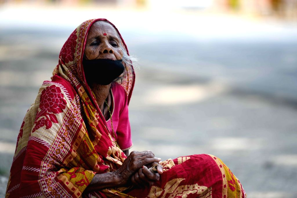 A lady wearing a mask sits at a footpath along a deserted Patna street during the extended nationwide lockdown imposed to mitigate the spread of coronavirus; on Apr 25, 2020.