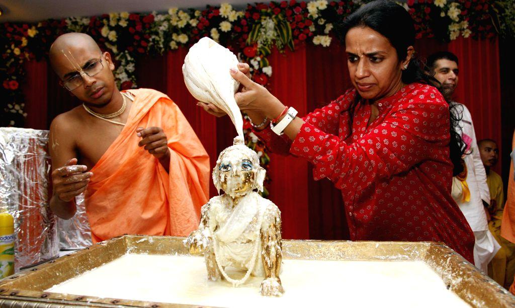 A lady worships lord Krishna on Janmashtami at ISKCON Temple in New Delhi on Aug 18, 2014.
