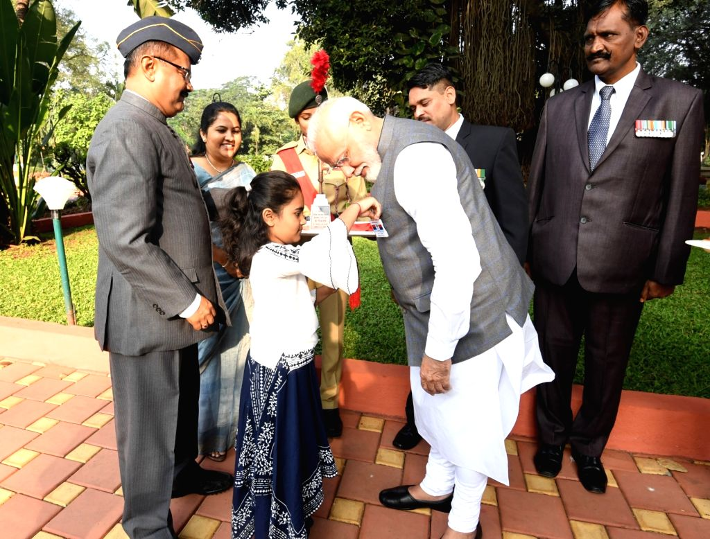 A little girl pins a flag on Prime Minister Narendra Modi on the occasion of Armed Forces Flag Day, in Pune on Dec 7, 2019. - Narendra Modi