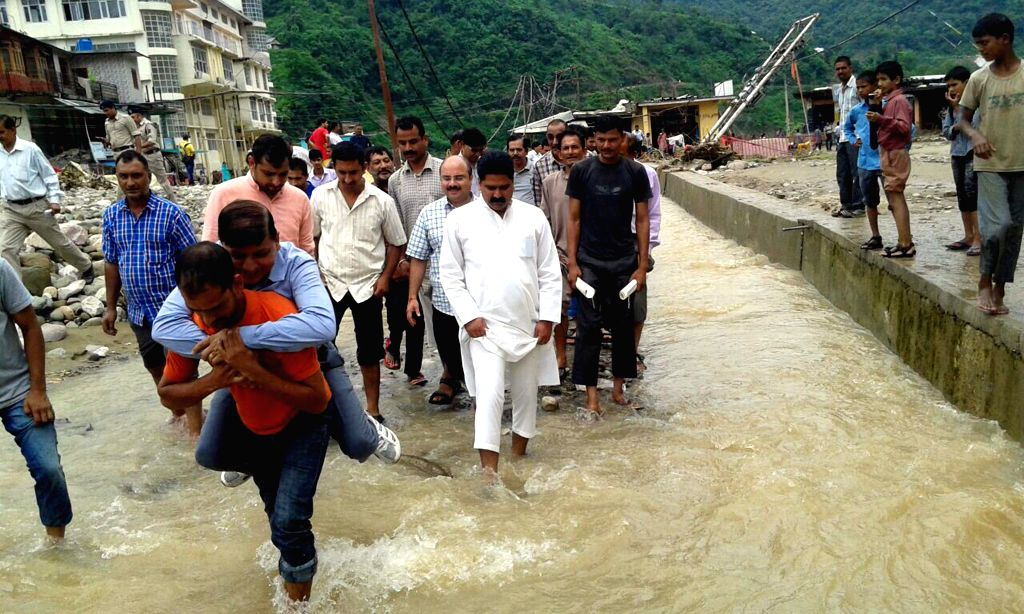 A local carries Himachal Pradesh Disaster Management Authority vice chairman Rajendra Rana on his back during his visit to flood-hit areas of Mandi district of the state.