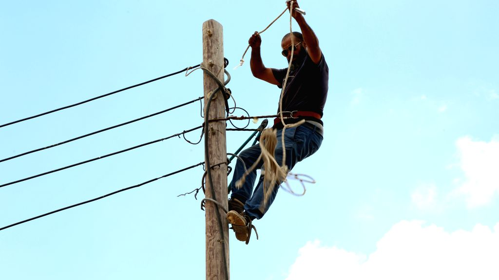 A maintenance worker from Libyan Electricity Company changes wires in Salah al-Din area, southern Tripoli, Libya, on June 23, 2020. Most Libyan cities, especially ...