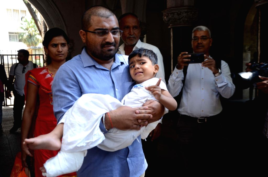 A man arrives at a hospital to get his son treated after a portion of an overhead pedestrian bridge outside the Chhatrapati Shivaji Maharaj Terminus came crashing down, in Mumbai on March 15, ...