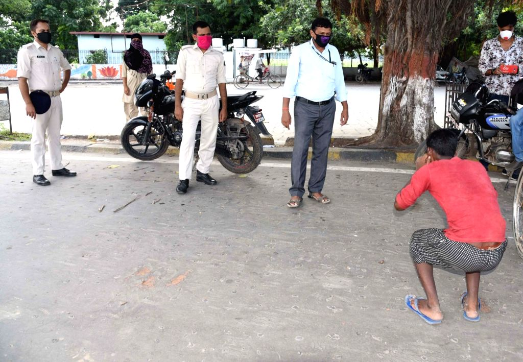 A man being made to perform sit-ups as punishment for not wearing mask in public space during a re-imposed COVID-19 lockdown in Patna on July 16, 2020.