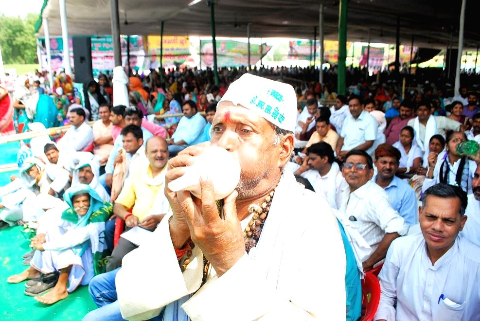 "A man blows a ""conch"" during a JD(U) rally in Varanasi on May 12, 2016."