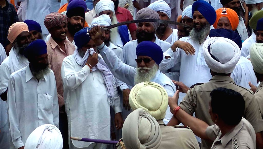 A man brandishes a sword as members of the newly-created Haryana Sikh Gurdwara Parbandhak Committee (HSGPC) clash with police near a gurdwara in a takeover bid in Kurukshetra on Aug 6, 2014.