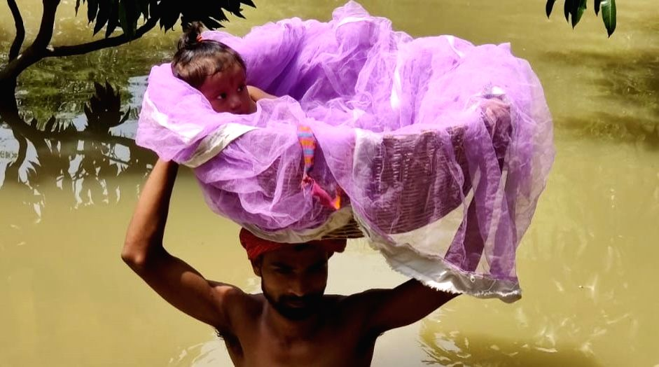 A man carries a child on his head to save the baby from the flood waters in Bihar's Sitamarhi, on July 19, 2019.