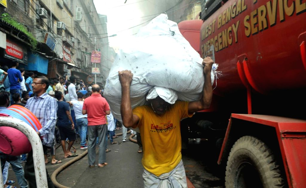 A man carries a sack to safe place from Bagri Market where a massive fire broke out around 2.45 a.m. in Kolkata on Sept 16, 2018.