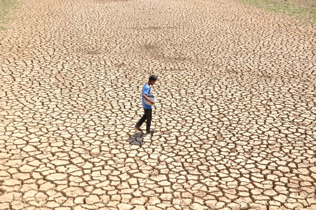 A man carries a water vessel as he walks on a patch of parched land near Ranchi on April 22, 2016.