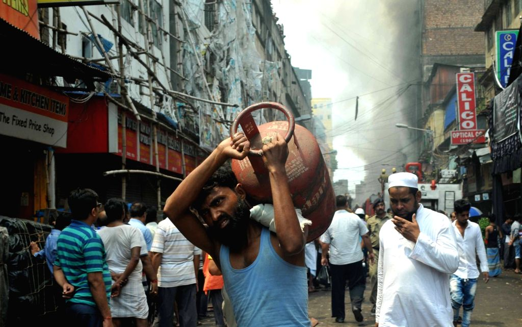A man carries an LPG cylinder to safe place from Bagri Market where a massive fire broke out around 2.45 a.m. in Kolkata on Sept 16, 2018.
