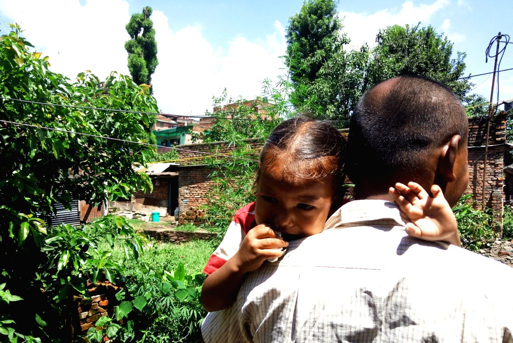 A man carries his child to safe place after an aftershock of 4.3 magnitude struck with an epicenter in the capital in Kathmandu, Nepal, Aug. 11, 2015. Nepalese ...