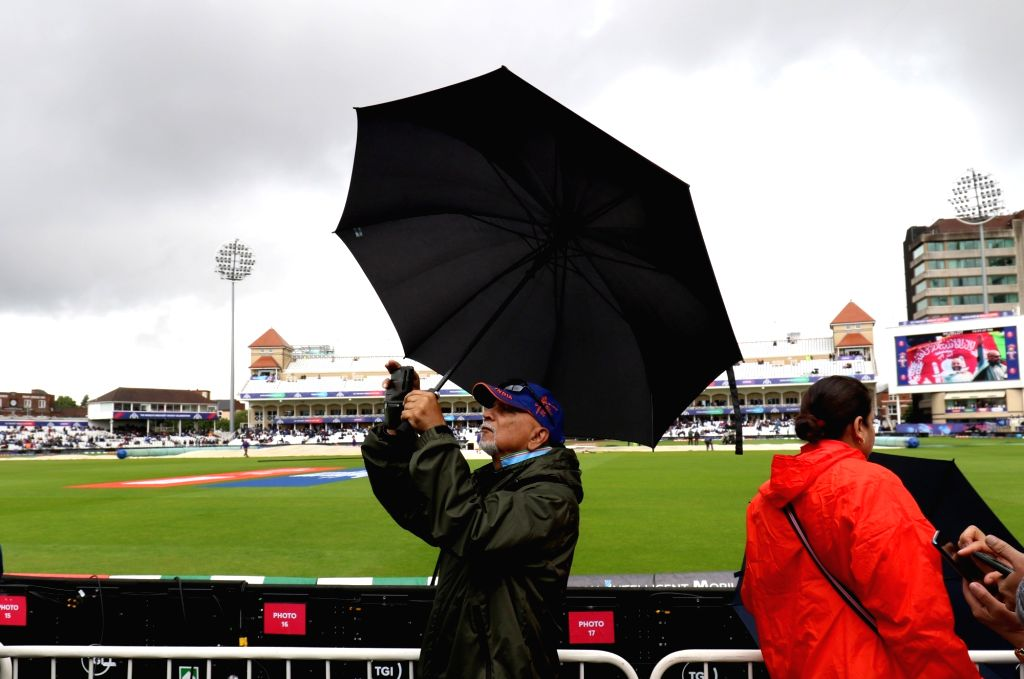 A man carrying an umbrella clicks pictures at Trent Bridge Cricket Ground ahead of the 18th Match of World Cup 2019 between India and New Zealand that has been delayed due to rains in ...