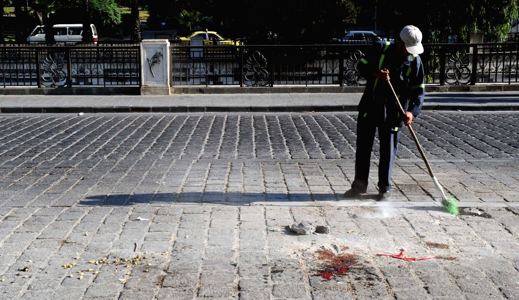 A man clears the explosion site in Damascus, capital of Syria, Aug. 12, 2015. At least one person was injured in a barrage of rebel rocket fire on the Syrian ...