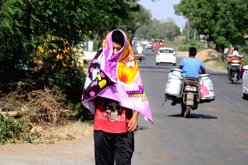 A man covers himself to avoid scorching sun on a hot day in Amritsar, on May 25, 2018.