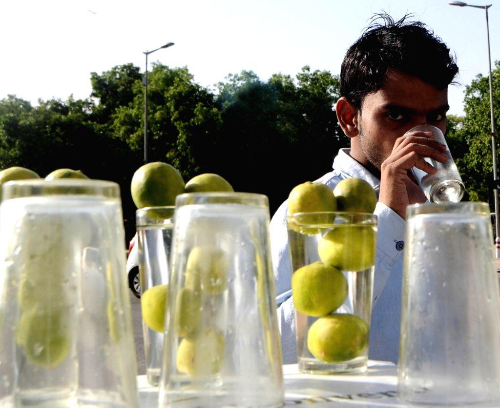 A man drinks lemonade on a hot summer day in New Delhi on June 8, 2019.