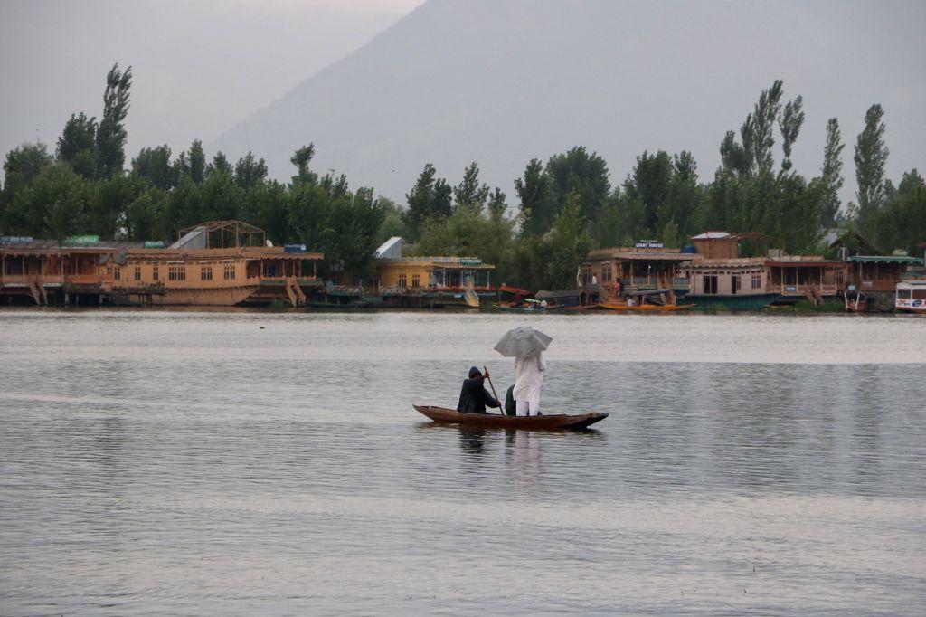 A man enjoys boat ride in the Dal Lake amidst rains in Srinagar on July 18, 2019.