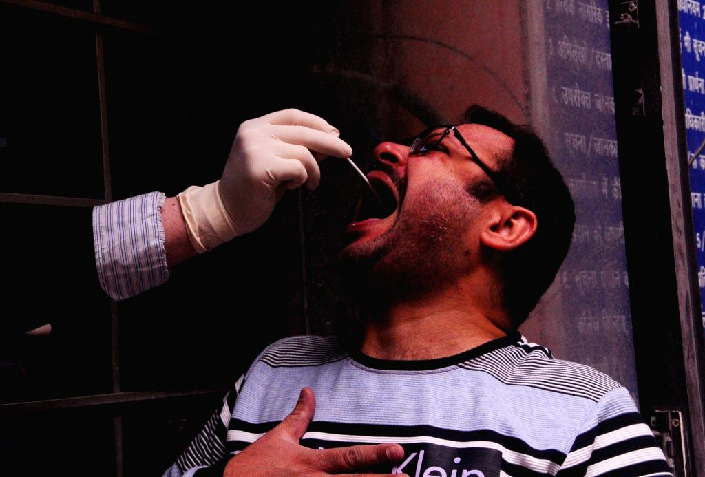 A man gives swab samples for COVID-19 testing at the District magistrate office (SDM) Lajpat Nagar, in New Delhi on Nov 24, 2020.