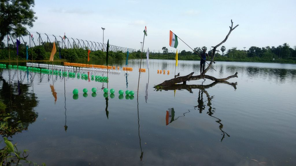 A man hangs a flag in the middle of a pond close to the border fencing in Agartala-Bangladesh border on 69th Independence Day, on Aug 15, 2015.