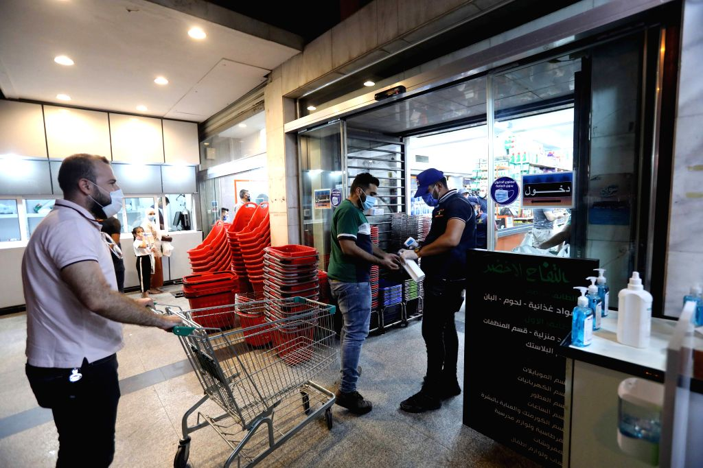 A man has his hands disinfected at the entrance to a shopping center in Baghdad, Iraq, Aug. 13, 2020. The Iraqi Health Ministry on Thursday recorded 3,841 new ...
