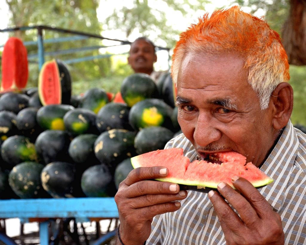 A man haves a watermelon to cool himself on a hot day in Bikaner on April 18, 2016.